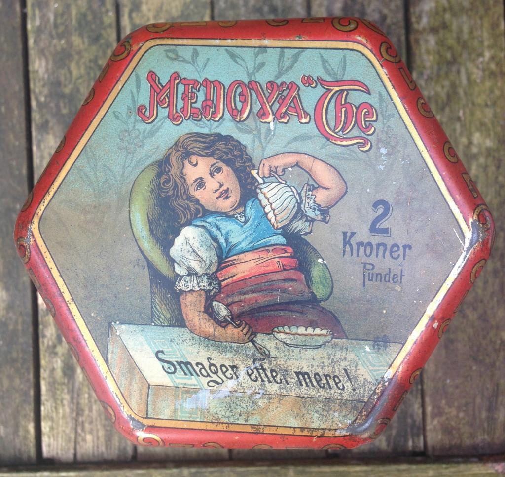 Låg fra Medova tedåse, med firmalogo fra 1907
