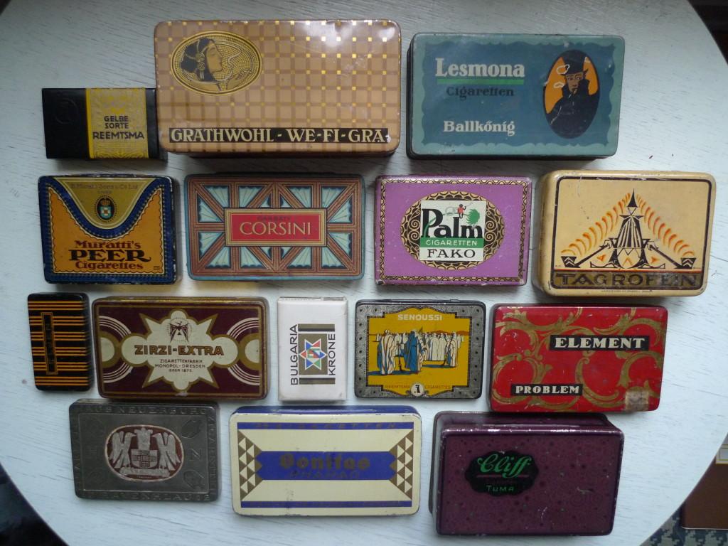 """Øverst tv: firma """"Reemtsma""""`s 10 stk """"Gelbe Sorte"""" fra 1921 (karton), design: Hans Domitzlaff. Dernæst 100 stks blikdåse til """"We-Fi-Gra""""-cigaretter med guldmundstykke fra kommanditselskabet W.F.Grathwohl i München ca 1910 (kender pt ingen angivelse af hvem som har designet dåsen), og øverst th: 50 """"Ballkönig"""" cigaretdåse fra Cigarettenfabrik Lesmona G.m.b.H. Bremen (også uden navngiven designer). 2. række fra oven yderst tv: 20 stks cigaretæske af mærket """"Peer"""" fra B.Muratti Sons & Co Ltd. G.M.B.H., dåsen signeret J-B (Martin Jacoby-Boy) datering ca 1910. På Garbàty`s 25 stk """"Corsini"""" cigaretæsken fra ca 1914 har Jacoby-Boy også været på spil. Designeren Julius Klinger tegner sig for 25 stk """"Fako""""-Gold fra cigaretfirmaet Eduard Palm Berlin og Hamborg fra ca 1910. Den yderste til højre i rækken har indeholdt 50 gram """"Tagrofein -Gold"""" pibetobak for tobaksfabrikant """"Tagro"""" Frankfurt A./M., det efter min smag ualmindelig udsøgte dåsedesign er signeret Bock. I næst nederste linie fra venstre ses lille blikæske begået af Hans Lindenstaedt ca 1912. Firmaet """"Josetti"""" har destribueret   5 stk """"Elgen""""-cigaretter på denne måde. Den efterfølgende grafisk spændende blikdåse til 25 stk Zirzi-Ekstra zigaretten fra Dresdener cigaretfabrikken """"Monopol"""" kan pt designmæssigt desværre ikke navngives. Ilse Lagerfeld har tegnet karton æsken til 10 """"Bulgaria Krone""""-cigaretter. Det har hun gjort for cigaretfabrikken """"Bulgaria"""" i Dresden ca 1930. Hans Domitzlaff har tegnet """"Senoussi"""" æskerne for """"Reemtzma"""", et firma der populært sagt """"åd"""" en betragtelig del af konkurrenterne op igennem tyverne. Denne æske er til 25 cigaretter og udsendtes første gang i 1923. Fabrikken Mahalla Problem afslutter rækken med den grafisk dristige 25 stk """"Element""""-cigaretter (pt designmæssigt unavngiven). Nederst tv: Oscar Hermann Werner Hadank har i midt tyverne sandsynligvis designet denne 12 stks """"Ravenklau""""-zigaretten for """"Haus Neuerburg"""" på bagsiden indslået: TROPEN-PACKUNG. Dåsen bærer Hadanks signatur cent"""