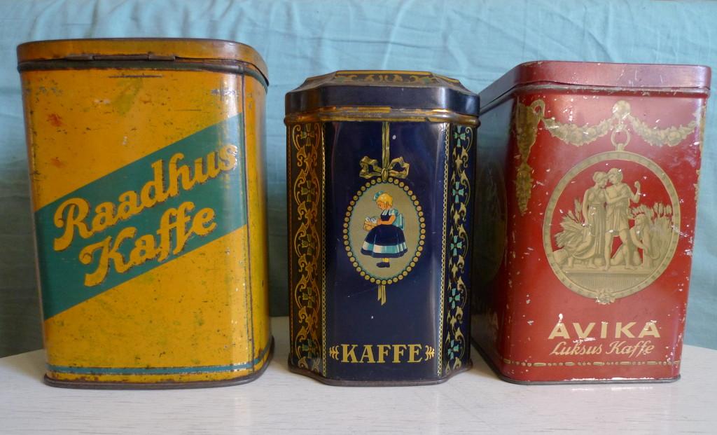 """Fra venstre ses A/S J.Lauritsen & Co`s kaffedåse til køkkenbrug, en af Irma`s mange ditto i midten, og th tilsvarende reklamerende for """"Avika"""" luksuskaffe."""